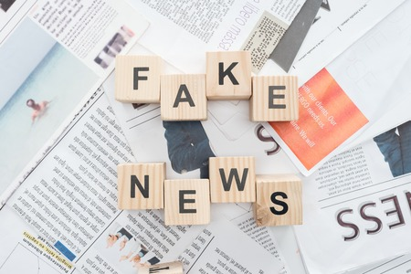 Photo pour top view of wooden cubes with words fake news on newspapers - image libre de droit