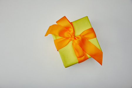 Foto de Top view of wrapped gift with orange bow isolated on grey background - Imagen libre de derechos