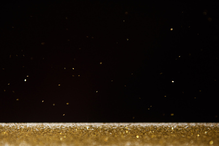 Foto de table with bright golden sparkles isolated on black - Imagen libre de derechos