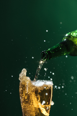 Photo pour pouring beer into glass with splashes and copy space isolated on green, st patrick day concept - image libre de droit