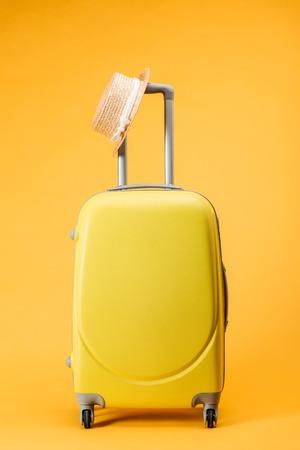 Foto de travel bag with wheels and straw hat on yellow background - Imagen libre de derechos