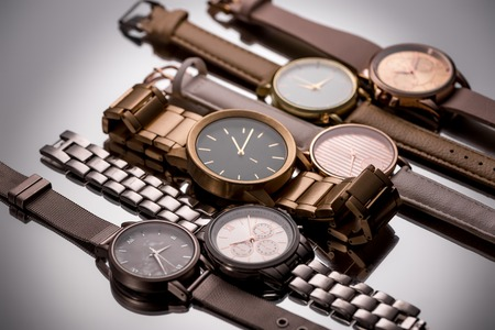 Foto de Luxury wristwatches with clock hands lying on grey background - Imagen libre de derechos