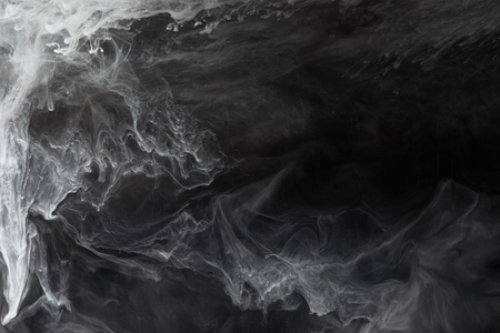 Photo pour Abstract flowing swirls of grey paint on black background - image libre de droit