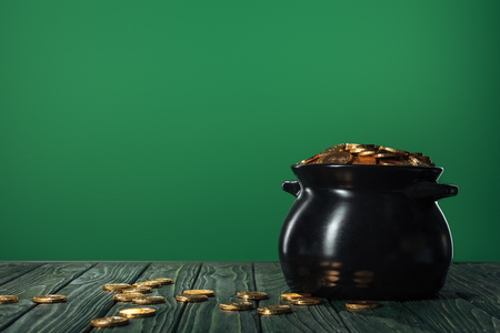 Foto de Golden coins in pot isolated on green with copy space, st patrick day concept - Imagen libre de derechos