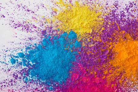 Foto de top view of explotion of yellow, purple, orange and blue holi powder on white background - Imagen libre de derechos