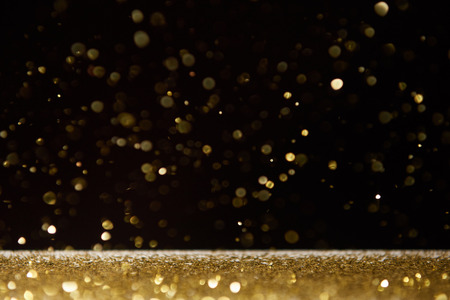 Foto de selective focus of golden shiny sparkles falling on table isolated on black - Imagen libre de derechos