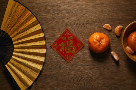 Foto de top view of fan, fresh ripe tangerines and decorative golden hieroglyph on wooden table - Imagen libre de derechos