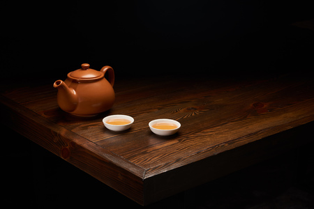 Foto de pot with traditional chinese tea and cups on wooden table isolated on black - Imagen libre de derechos
