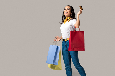 Foto de Smiling trendy dressed asian woman carrying colorful shopping bags and holding credit card isolated on grey - Imagen libre de derechos