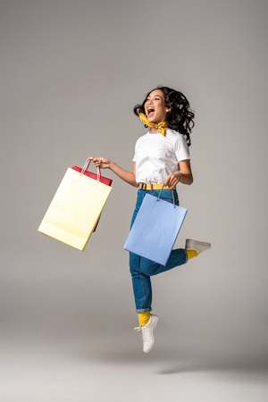 Photo for Beautiful young asian woman jumping up with happy smile while holding colorful shopping bags on grey - Royalty Free Image