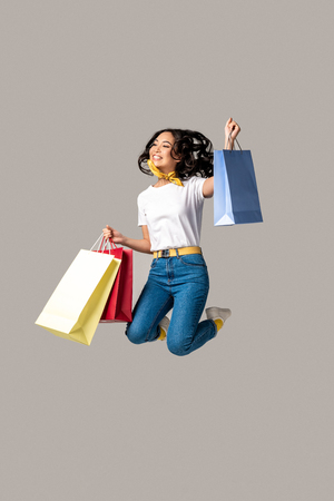 Foto de Excited asian woman holding colorful shopping bags and happily jumping with one raised hand isolated on grey - Imagen libre de derechos