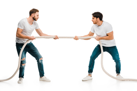 Foto de young men pulling rope and playing tug of war isolated on white - Imagen libre de derechos