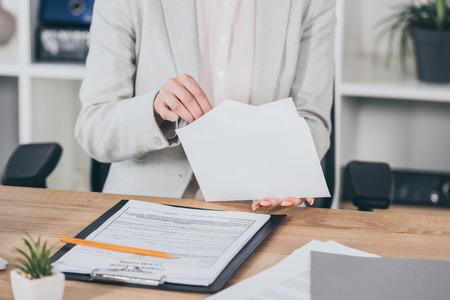 Photo pour cropped view of businesswoman putting money into open envelope while sitting at desk, compensation concept - image libre de droit