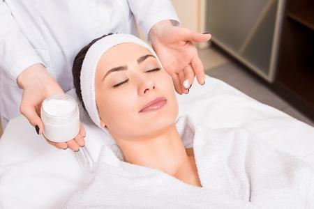 Photo pour beautician holding cosmetic cream bottle and puting it on woman face at beauty salon - image libre de droit