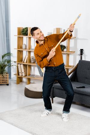 Foto de handsome man dancing with broom in modern living room - Imagen libre de derechos