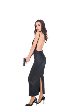 Photo pour beautiful elegant killer in black dress holding gun, isolated on white - image libre de droit