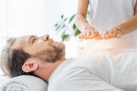 Photo for cropped shot of bearded man looking up while receiving reiki treatment - Royalty Free Image