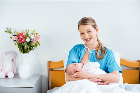 Photo pour happy young mother sitting in bed and smiling at camera while breastfeeding newborn baby - image libre de droit