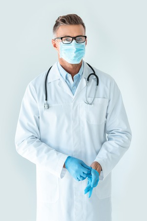 Photo pour handsome doctor in medical mask wearing medical gloves and looking at camera isolated on white - image libre de droit