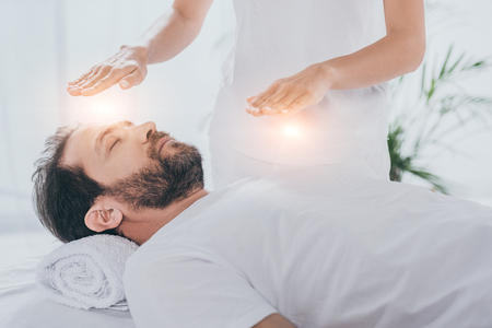 Photo pour cropped shot of bearded man with closed eyes receiving reiki healing treatment - image libre de droit