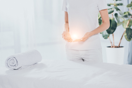 mid section of reiki healer with light energy in hands standing near white massage table