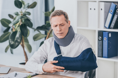 middle aged worker holding broken arm wile sitting at table with document in office, compensation concept