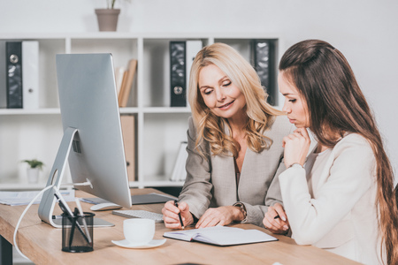 Photo pour smiling female business mentor pointing at notebook and working with young colleague in office - image libre de droit