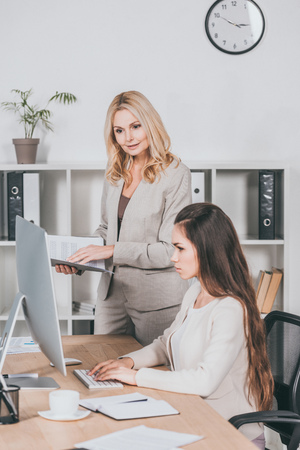 Photo pour mature business mentor with folder and young businesswoman looking at desktop computer in office - image libre de droit