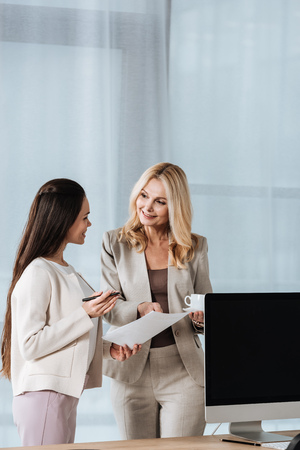 beautiful smiling businesswomen standing and discussing papers together in office