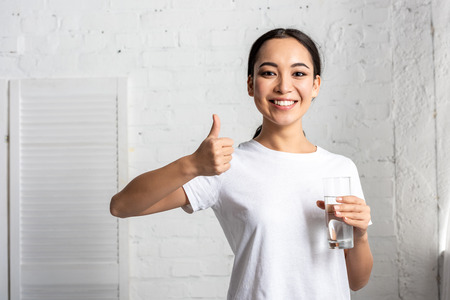 Foto de smiling young asian woman in white t-shirt holding glass of water and showing thumb up - Imagen libre de derechos