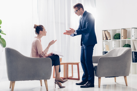 Foto de irritated businessman standing and gesturing while giving interview to journalist in office - Imagen libre de derechos