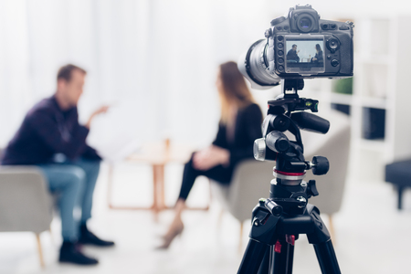 Photo pour businesswoman in suit giving interview to journalist in office, camera on tripod on foreground - image libre de droit