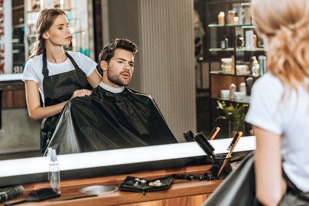 Foto de female hairstylist cutting hair to handsome young man in beauty salon - Imagen libre de derechos