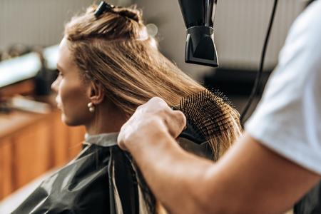 Foto für cropped shot of hairdresser drying hair to attractive girl in beauty salon - Lizenzfreies Bild