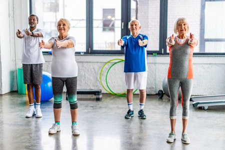 Foto de cheerful multiethnic senior sportspeople synchronous exercising at sports hall - Imagen libre de derechos