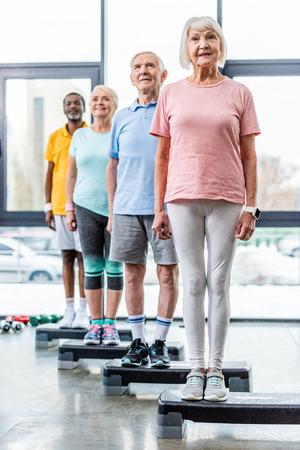 Foto de cheerful multiethnic senior athletes standing on step platforms at gym - Imagen libre de derechos