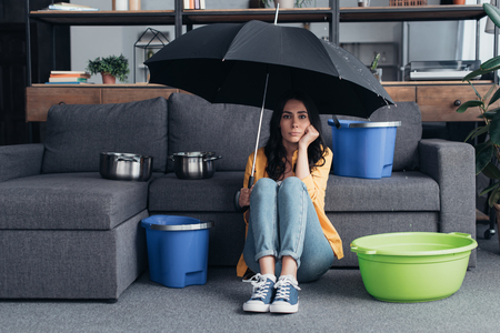 Foto per Pensive brunette girl sitting on floor with umbrella - Immagine Royalty Free