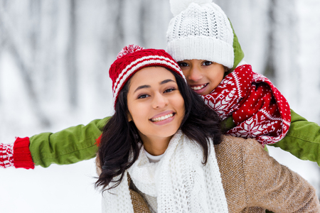 Photo pour beautiful african american woman piggybacking cheerful daughter and looking at camera in winter park - image libre de droit