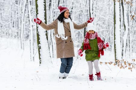 Foto de beautiful african american woman and cute preteen daughter having fun in winter park - Imagen libre de derechos