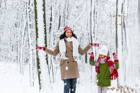cheerful african american woman and preteen daughter throwing up snow in winter park