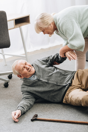 old woman helping to stand up husband who falled down on floor with walking stick