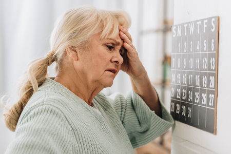 Photo pour upset woman with gray hair touching head and looking at wall calendar - image libre de droit