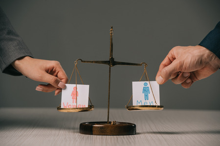 Foto de cropped view of businesspeople with male and female signs on scales of justice, gender equality concept - Imagen libre de derechos