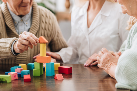 Foto de cropped view of caregiver sitting with retired man and woman and playing with wooden toys - Imagen libre de derechos