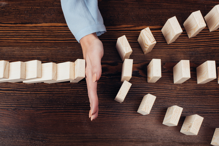 Foto de cropped view of woman preventing wooden blocks from falling at desk - Imagen libre de derechos