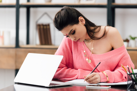 Foto de indian woman with bindi writing in notebook and studying with laptop at home - Imagen libre de derechos