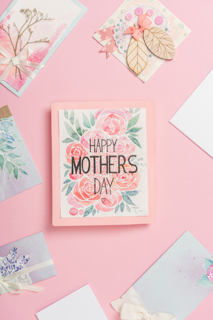 Photo for happy mothers day greeting card with flowers, and various mothers day postcards arranged around on pink background - Royalty Free Image