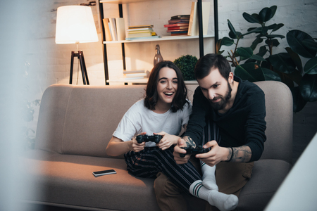 selective focus of beautiful young couple sitting on couch with joysticks and playing video game in living room