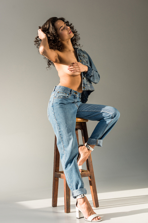 Foto de sexy naked woman with curly hair covering breast with hand while sitting on chair on grey background - Imagen libre de derechos