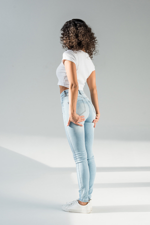 Photo pour back view of woman standing in tight blue jeans on grey background - image libre de droit